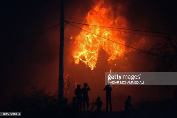Iraqi protesters watch on official building in flames as they demonstrate against the government and the lack of basic services in Basra on September...