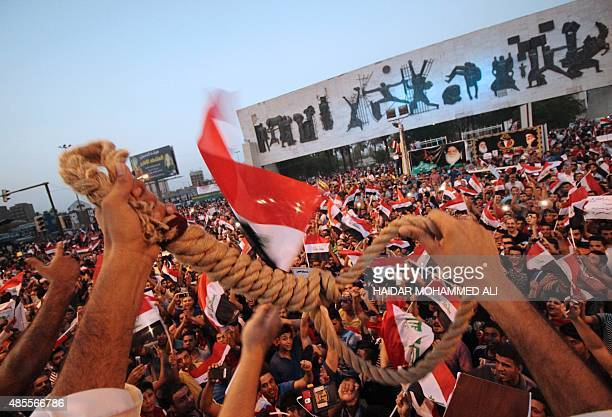 Iraqi protesters wave a hangman's noose and their national flags during a demonstration against corruption in Baghdad's Tahrir Square on August 28...