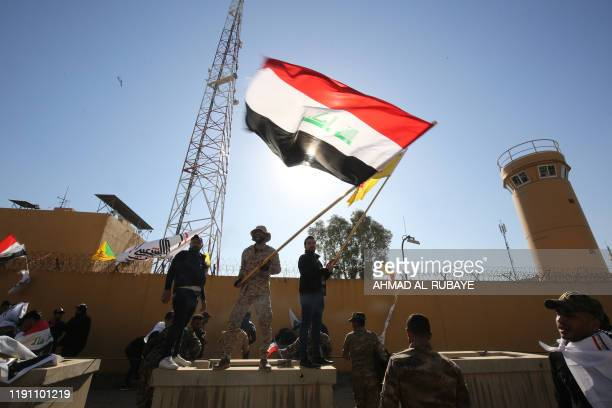 TOPSHOT Iraqi protesters wave a national flag in front of the outer wall of the US embassy in Baghdad's Green Zone during an angry demonstration on...