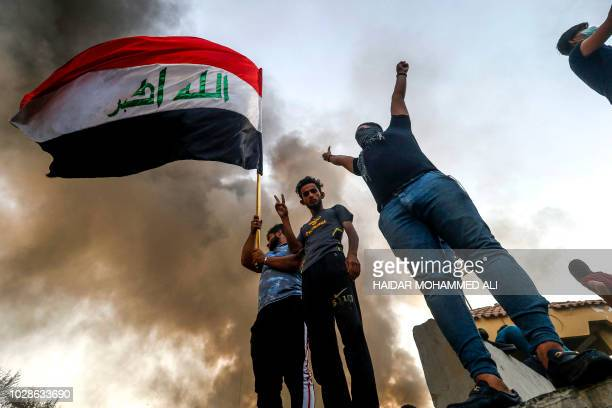 Iraqi protesters wave a national flag while demonstrating outside the burntdown local government headquarters in the southern city of Basra on...