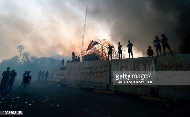 Iraqi protesters wave a national flag while demonstrating outside the burnt-down local government headquarters in the southern city of Basra on...