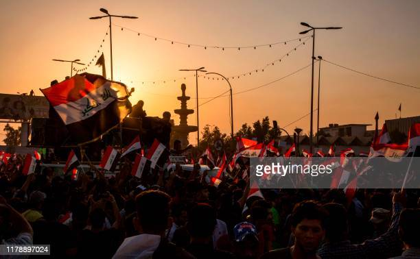 Iraqi protesters wave national flags as they gather during an anti-government demonstration outside the local government headquarters in the southern...