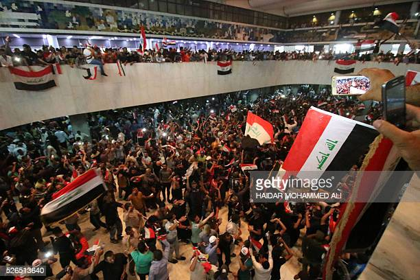 TOPSHOT Iraqi protesters wave national flags as they gather inside the parliament after breaking into Baghdad's heavily fortified 'Green Zone' on...