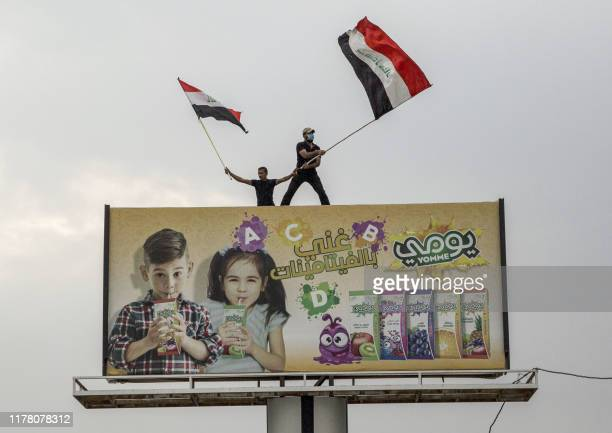 Iraqi protesters wave national flags as they stand atop a billboard during an anti-government demonstration outside the local government headquarters...