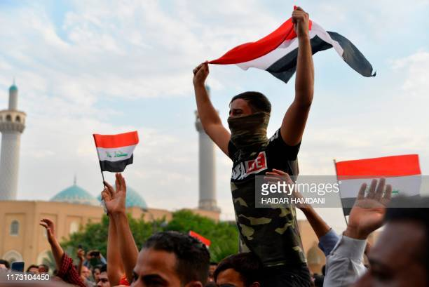 Iraqi protesters wave the national flag during a demonstration against state corruption failing public services and unemployment in the central Iraqi...