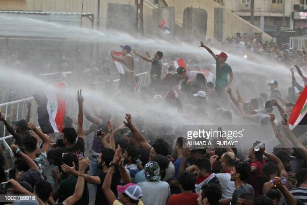 Iraqi protesters waving national flags are being sprayed with water cannon by security forces during a demonstration against unemployment and a lack...