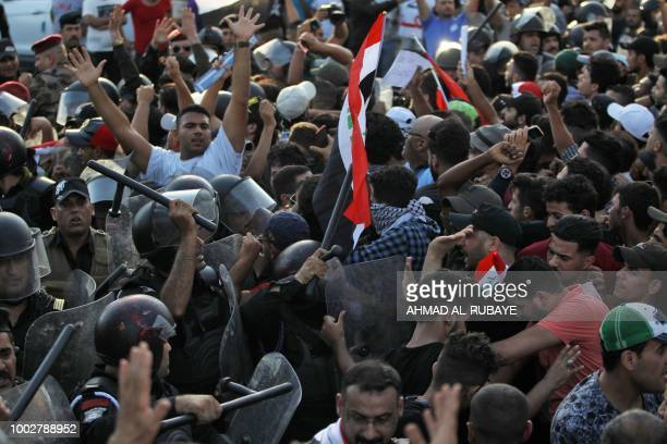 Iraqi protesters waving national flags clash with security forces during a demonstration against unemployment and a lack of basic services in the...