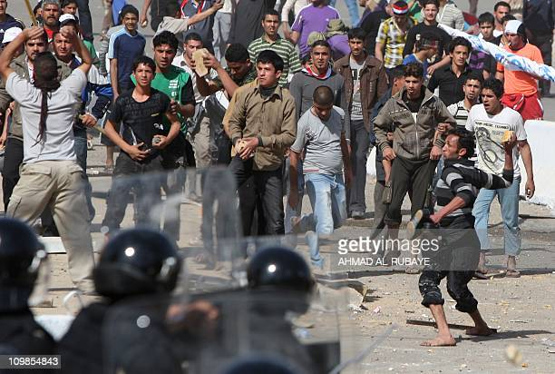 Iraqi protestors trow stone at Iraqi riot police on February 25 2011 at Baghdad's Tahrir square following a rally calling for improved public...