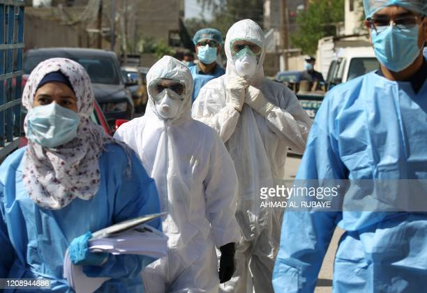 Iraqi public hospital specialised doctors gather in a street before testing residents for COVID-19 in the capital Baghdad's suburb of Sadr City on...