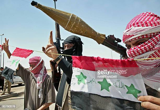 Iraqi rebels heavily armed stand behind their national flag in a street of the restive city of Fallujah 01 May 2004 Even as their units pull out of...