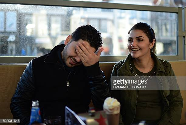 Iraqi refugees Ahmad and Alia share a joke as they sit in cafe in Leeuwarden The Netherlands on December 8 2015 After Ahmad and Alia survived a bomb...
