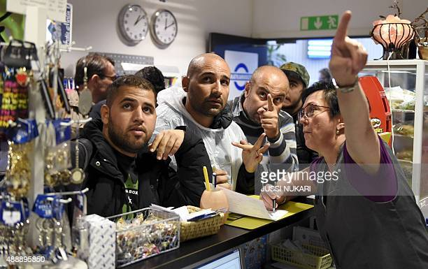 Iraqi refugees buy train tickets to Turku from a public transport centre in Tornio northwestern Finland on September 18 2015 Finland expects a total...