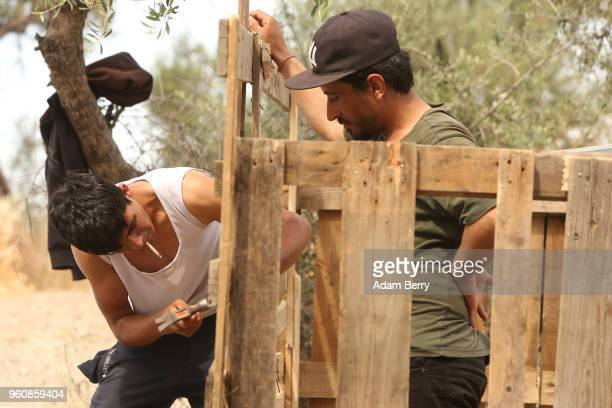 Iraqi refugees construct a makeshift shelter at the Moria refugee camp on May 20 2018 in Mytilene Greece Despite being built to hold only 2500 people...