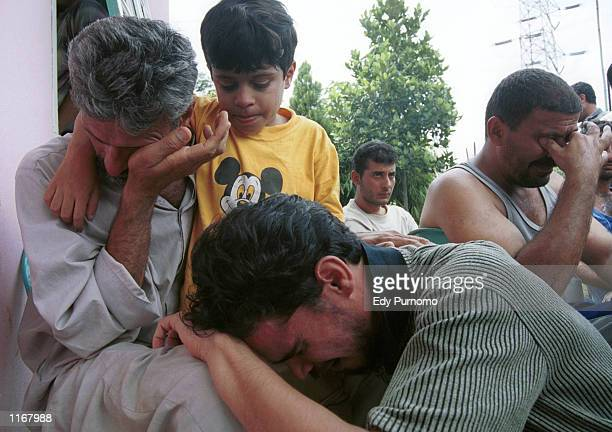 Iraqi refugees cry over the loss of family members at a refugee camp October 24 2001 in Bogor West Java Indonesia Some 350 people drowned when a boat...