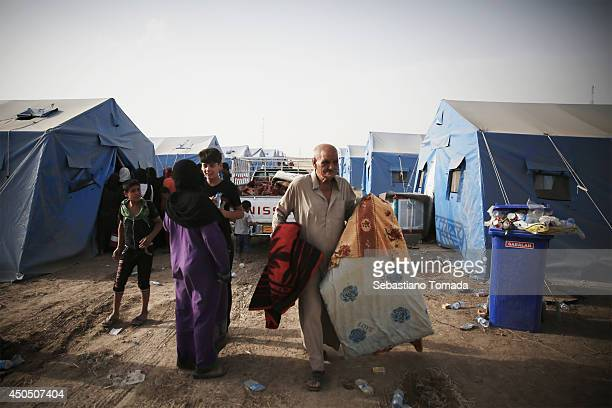 Iraqi refugees gather food and blankets in a makeshift camp at a Kurdish checkpoint in Kalak after fleeing from the city of Mosul which has been...