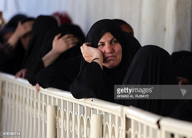Iraqi refugees who fled Ramadi after it was seized by the Islamic State group await their turn to receive iftar meals during Muslim holy month of...
