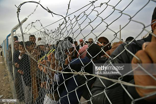 Iraqi refugees who fled the Iraqi city of Mosul due to the fighting between government forces' and Islamic State group's jihadists look from behind a...