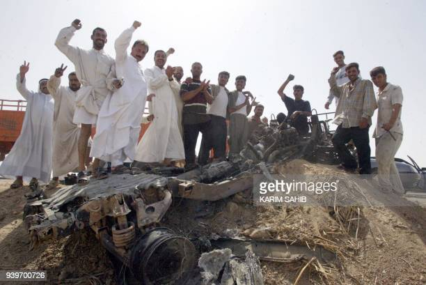 Iraqi residents chant Allah Akbar proSaddam and antiUS slogans in celebration atop a destroyed US military vehicle 12 September 2003 in the...