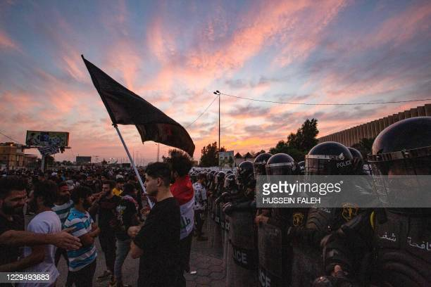 Iraqi riot police form a shield as demonstrators gather near the local administration building in the southern city of Basra on November 6 during an...