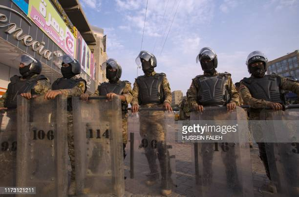 Iraqi riot police stand guard as protestors take part in a demonstration against state corruption, failing public services and unemployment, on...