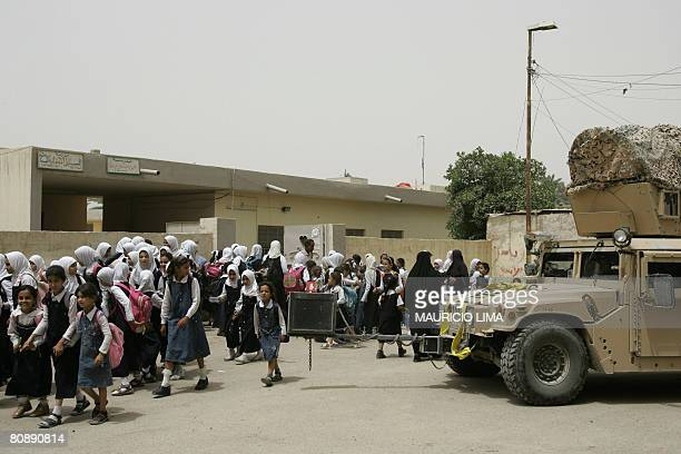 Iraqi schoolgirls walk past a US military Humvee belonging to the 3rd Battalion 320th Field Artillery as they leave from school in downtown...