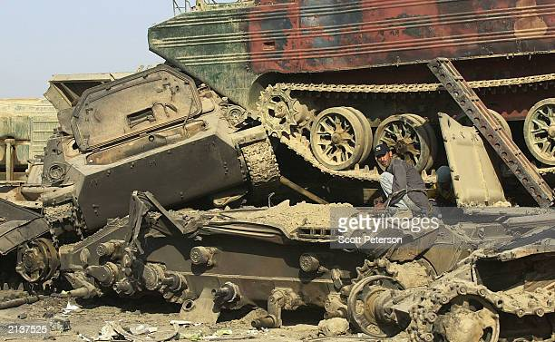 """Iraqi scrap dealers and looters scavenge the """"tank graveyard"""" of Iraqi military hardware and vehicles created by U.S. Troops June 30, 2003 in Doura,..."""