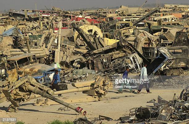 """Iraqi scrap dealers and looters take their haul away after scavenging the """"tank graveyard"""" of Iraqi military hardware and vehicles created by U.S...."""
