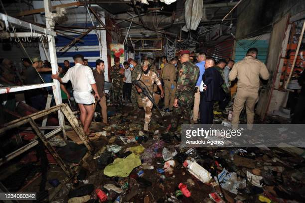 Iraqi security forces and citizens inspect the site after a blast at Al-Wahilat market in Sadr district of Baghdad, Iraq on July 19, 2021. It is...