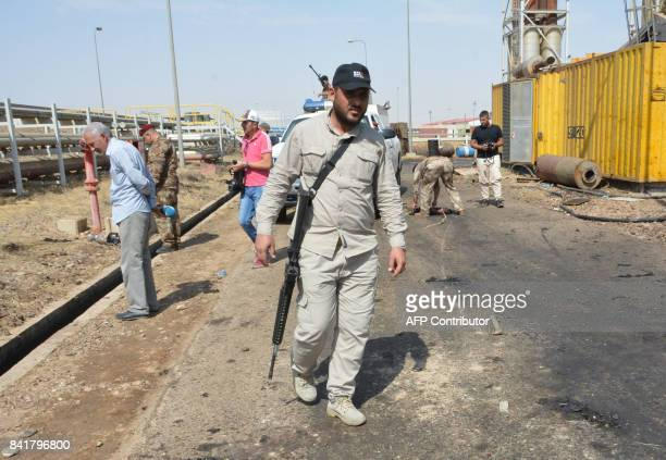 Iraqi security forces and members of the Saraya alSalam a group formed by Iraqi Shiite Muslim cleric Moqtada alSadr inspect the site of suicide...