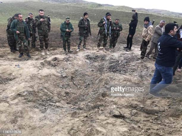 Iraqi security forces and soldiers gather to inspect the site after Iran's Islamic Revolutionary Guard Corps targeted Ain alAsad airbase in Iraq a...