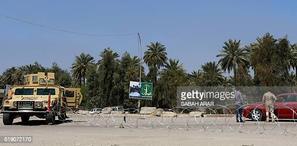 Iraqi security forces check vehicles at the site of a suicide attack targeting a joint police and army checkpoint near Muthana Brdige in northern...