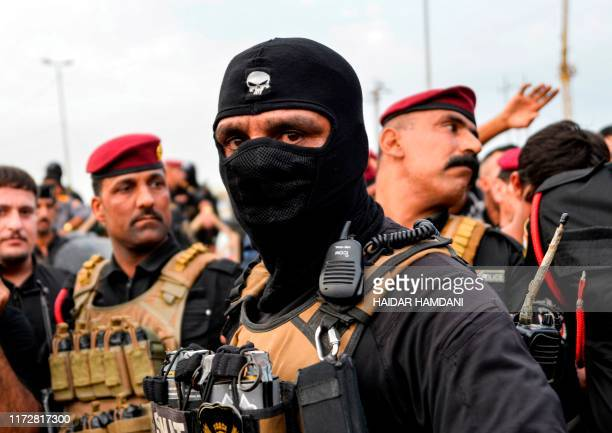 Iraqi security forces confront protesters during a demonstration against corruption and lack of basic services in the central Iraqi shrine city of...