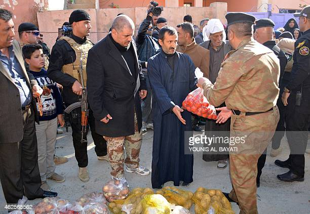 Iraqi security forces distribute bags of food during a visit with officials in the village of Brawna outside the town of Muqdadiyah in the Diyala...