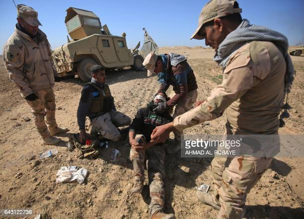 TOPSHOT Iraqi security forces evacuate a comrade wounded in an explosivesladen vehicle attack claimed by Islamic State group as the troops advance...