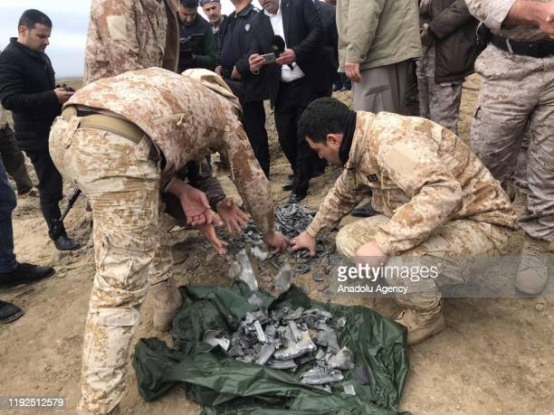 Iraqi security forces find and collect the pieces of missiles as they gather to inspect the site after Iran's Islamic Revolutionary Guard Corps...