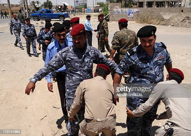 Iraqi security forces frisk comrades outside a polling station in Ramadi on June 17 2013 as policemen and soldiers vote in provincial polls ahead of...