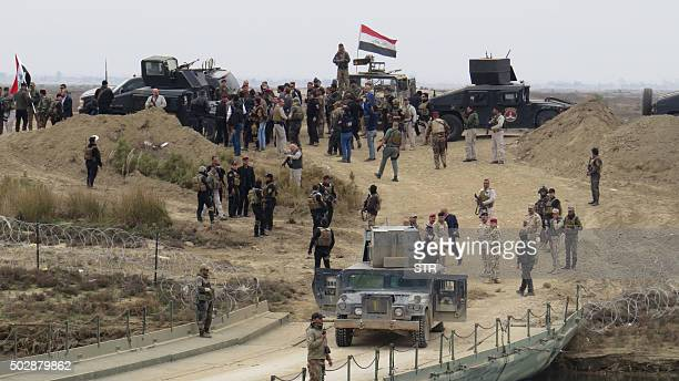 Iraqi security forces gather near a temporary bridge built by the corps of engineers in the Iraqi army south of Ramadi during a visit by Iraqi Prime...
