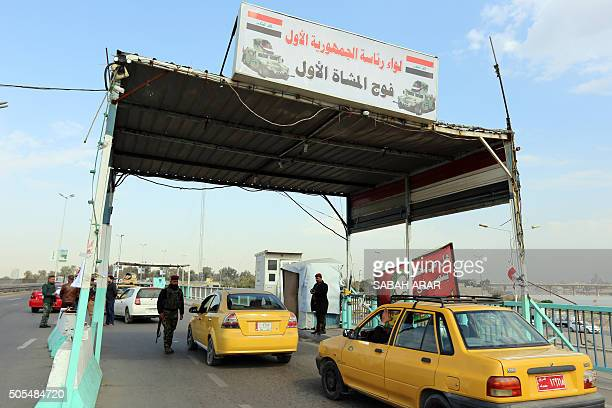Iraqi security forces inspect a car at a checkpoint on the main road from Baghdad's central Jaderiyah district to Dora on the southern outskirts of...