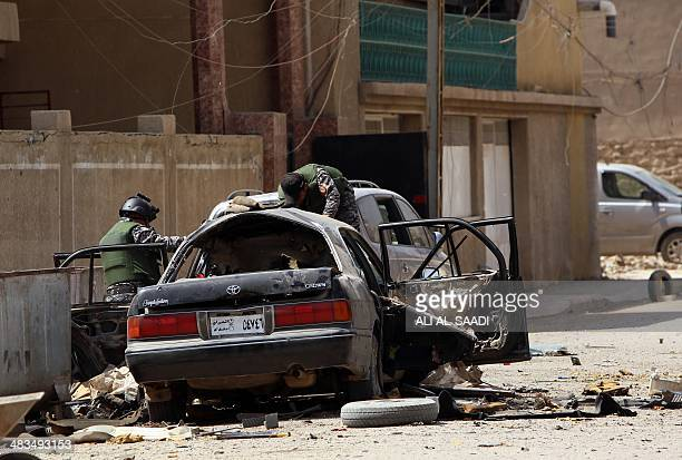 Iraqi security forces inspect a destroyed car at the site of an explosion in Baghdad on April 9 2014 Six car bombs rocked mainly Shiitepopulated...