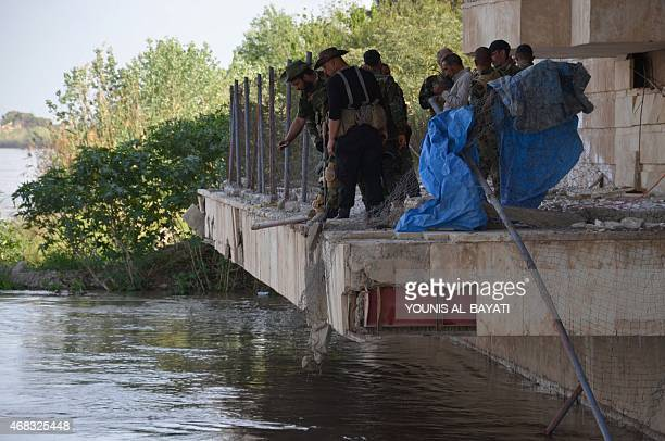 Iraqi security forces inspect a Tigris river waterfront in Tikrit on April 1 which is believed to be the place of a June 2014 massacre also know as...