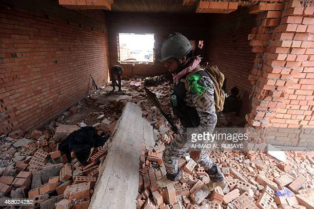 Iraqi security forces inspect the inside of a damaged house in the southern entrance of the city of Tikrit on March 29 2015 during a military...