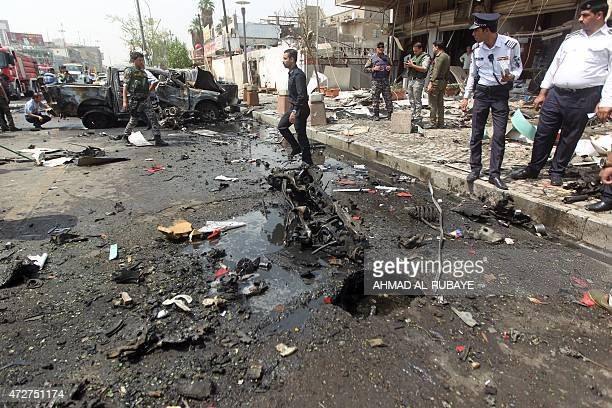 Iraqi security forces inspect the scene of a car bomb blast targeting Shiite pilgrims on an annual march to a Baghdad shrine which killed on May 9...