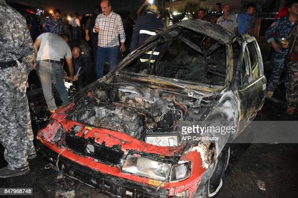 Iraqi security forces inspect the scene of a car bomb explosion that targeted a shop selling alcohol in the mainly Kurdish Iraqi city of Kirkuk on...