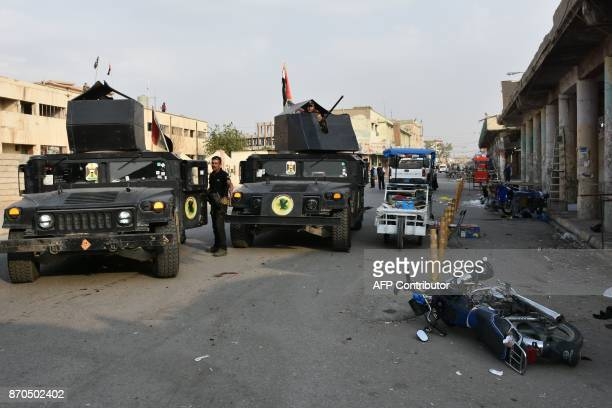 Iraqi security forces inspect the scene of a twin suicide attack at shopping area in Iraq's disputed Kirkuk city on November 5 2017 The attackers...