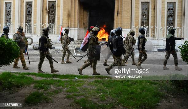 Iraqi security forces look at flames on a door of the shrine dedicated to the late Iraqi Shiite Ayatollah Mohammed Baqir alHakim in the southern...