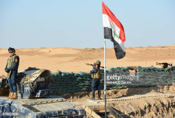 Iraqi security forces members hold a position as they advance towards the Salaheddine province in the western desert bordering Syria on November 26...