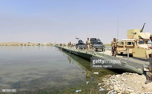 Iraqi security forces members stand guard on the temporarily constructed bridge will be used to dispatch military deliveries on Tigris River...