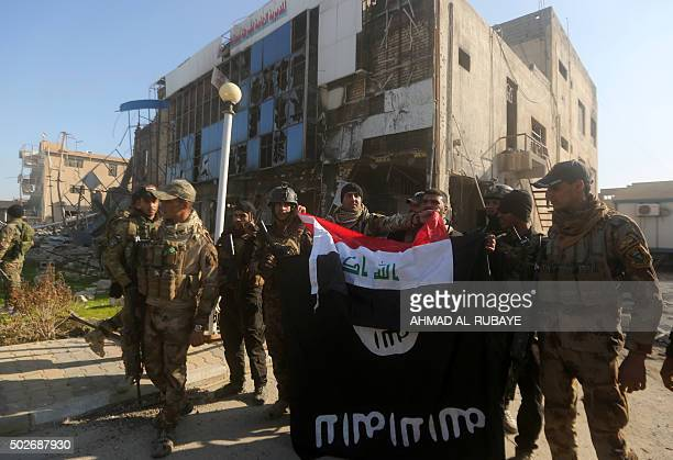 Iraqi security forces place the Iraqi flag above the Islamic State group flag as they pose for a picture on December 28 2015 in front of the Anbar...