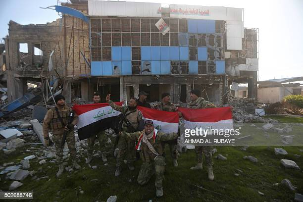 Iraqi security forces pose for pictures with their national flag on December 28 2015 in front of the heavily damaged Anbar police headquarters after...