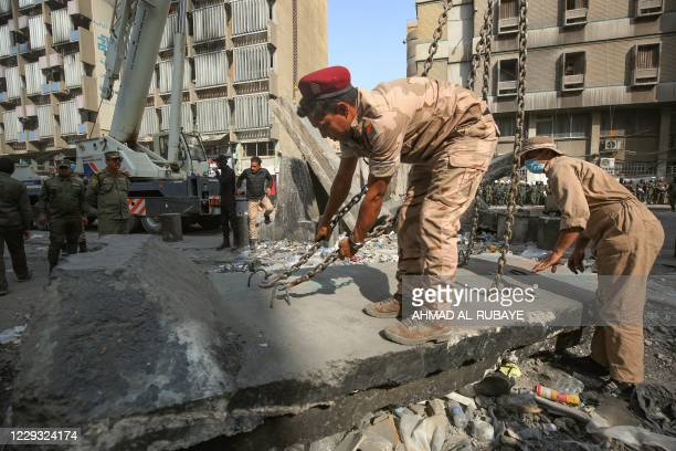 Iraqi security forces remove concrete blocks in the capital Baghdad's Tahrir Square on October 28 during a cleanup operation allowing roads around...